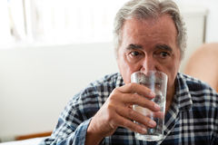 Senior man drinking water in nursing home. Senior man drinking water while sitting in nursing home Royalty Free Stock Image