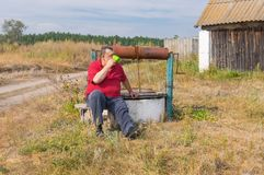 Senior man drinking water sitting on a bench near an old draw-well. In rural village in Poltavskaya oblast, Ukraine royalty free stock image