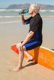Senior man drinking water while sitting on surfboard. At beach Royalty Free Stock Images