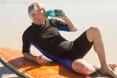 Senior man drinking water while sitting by surfboard. At beach Stock Photography