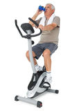 Senior man drinking water on stationary bike Royalty Free Stock Images