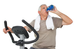 Senior man drinking water on stationary bike Stock Photography
