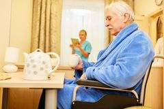 Senior man drinks coffee in assisted living. Senior men drinks coffee in assisted living in his senior citizen home royalty free stock photo