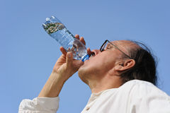 Senior man drinks water from a bottle Stock Photos