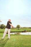 Senior man driving ball towards on course Stock Photos