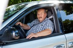 Senior man driving a car. Portrait of an elderly man driving a car Royalty Free Stock Images