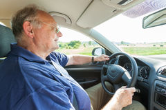 Senior man driving a car. Through the countryside, wide angle shot from the passenger perspective Royalty Free Stock Photography