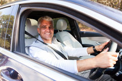 Senior man driving car. Handsome senior man driving his new car royalty free stock images