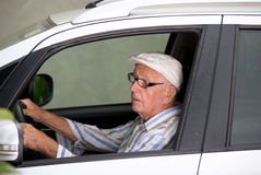 Senior man driving car. Retired elder man with glasses driving gray car Royalty Free Stock Photography
