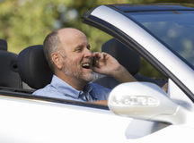 A senior man driving a car whilst on a cell phone Royalty Free Stock Image