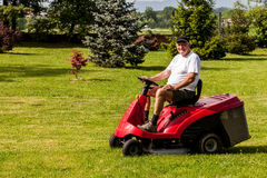 Senior man driving a red lawn mower Royalty Free Stock Images