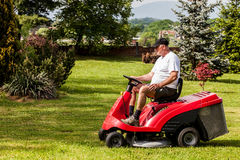 Senior man driving a red lawn mower Royalty Free Stock Photo
