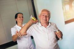 Senior man with dumbbells in rehab Stock Photos