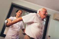 Senior man with dumbbells in rehab Stock Images