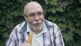 Senior man eat carrot. Active retirement, elderly bearded man with glasses contagiously laughs and eat carrot stock video