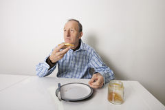 Senior man eating bread spread with sweet jelly jam at table Royalty Free Stock Photos