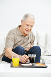 Senior man eating breakfast Royalty Free Stock Photos