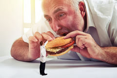 Senior man eating burger Royalty Free Stock Photography