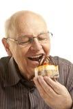 Senior man eating a cake Stock Images