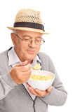 Senior man eating cereal with a metal spoon stock photos