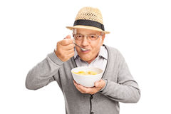Senior man eating cereal with a spoon. And looking at the camera isolated on white background Stock Photos