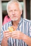 Senior man eating fish Royalty Free Stock Photo