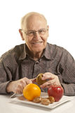 Senior man eating fresh fruit Stock Images