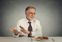 Senior man eating fresh salad avoiding fatty pizza Royalty Free Stock Images