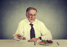 Senior man eating fresh vegetable salad avoiding fatty pizza. Healthy diet nutrition choices concept Stock Image