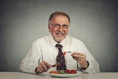 Senior man eating fresh vegetable salad. Happy senior man eating fresh vegetable salad Royalty Free Stock Photo