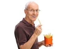 Senior man eating fries stock photo