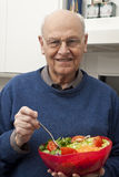 Senior man eating a healthy salad. At the kitchen Stock Images
