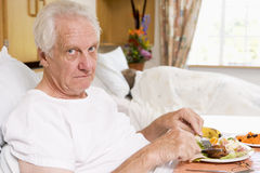 Senior Man Eating Hospital Food In Bed Stock Images
