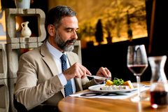 Senior man eating lunch in restaurant. Portrait of senior man eating lunch in restaurant stock images