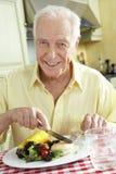 Senior Man Eating Meal In Kitchen Stock Photo