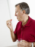 Senior man eating pills Stock Images