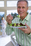 Senior man eating salad on plate at home, mature woman in background, focus on man, smiling, portrait Royalty Free Stock Photography