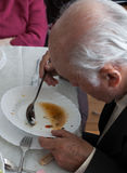 Senior man eating a soup intdoor Stock Images