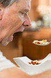 Senior man eating a spoon of vitamins stock images