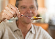 Senior man eating a spoon of vitamins Stock Image