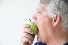 Older man bites into pear Royalty Free Stock Photo
