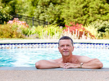 Senior man by edge of swimming pool. Senior male relaxing by the side of a modern swimming pool in back yard garden and facing the camera with smile Royalty Free Stock Photography