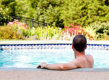 Senior man by edge of swimming pool. Senior male relaxing by the side of a modern swimming pool in back yard garden and facing away from the camera Royalty Free Stock Photos