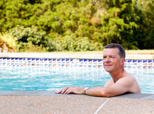 Senior man by edge of swimming pool. Senior male relaxing by the side of a modern swimming pool in back yard garden and facing the camera with smile Stock Image