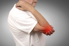 Senior man with elbow inflammation colored in red suffering from pain. Closeup senior man with elbow inflammation colored in red suffering from pain and Stock Photo