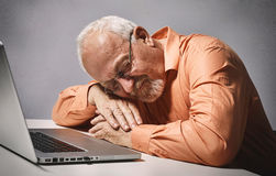 Senior man. Elderly man sleeping with laptop computer over gray background Royalty Free Stock Photography