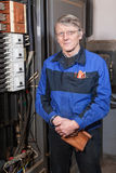 Senior man electrician in blue uniform standing near high voltage box Stock Photo