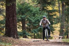 A senior man with electrobike cycling outdoors on a road in park in autumn. An active senior man with electrobike cycling outdoors on a road in park in autumn stock image