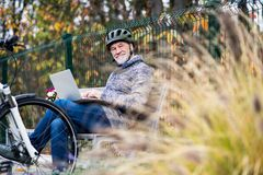 A senior man with electrobike sitting on a bench outdoors in town, using laptop. A senior man with electrobike sitting on a bench outdoors in town in autumn stock images