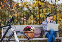 Senior man with electrobike sitting on a bench outdoors in town, using laptop and smartphone. royalty free stock photo